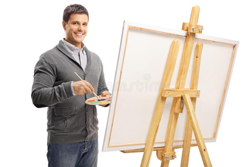 Handsome young man painting on a canvas. Isolated on white background royalty free stock photos