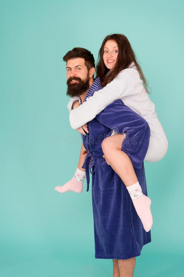 Handsome young man piggybacking beautiful woman. Couple in bathrobes having fun turquoise background. Lets stay at home. Handsome young men piggybacking royalty free stock image
