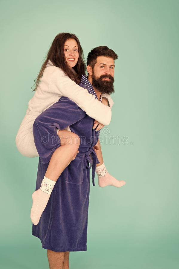 Handsome young man piggybacking beautiful woman. Couple in bathrobes having fun turquoise background. Lets stay at home. And have fun. They always have fun royalty free stock image