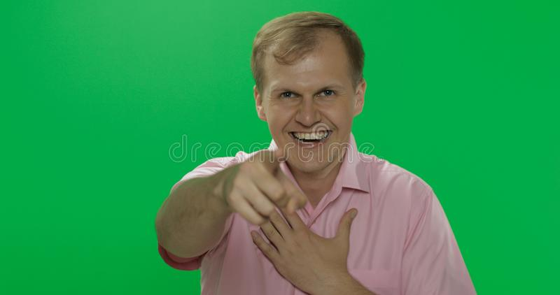 Handsome young man in pink shirt laughing. Chroma key royalty free stock photo