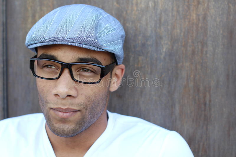 A handsome young man in plain clothes wearing hat and glasses royalty free stock photo