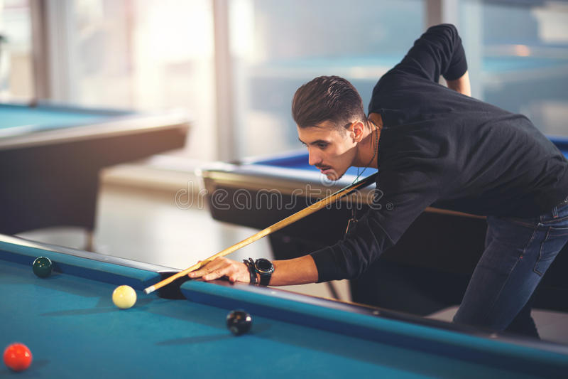 Handsome young man playing pool in pub. Handsome man playing pool in pub royalty free stock photos