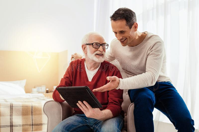 Handsome young man pointing on tablet. What is your attitude. Positive delighted pensioner keeping smile on his face and wrinkling forehead while looking aside stock image