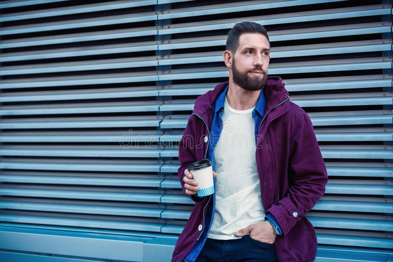 Handsome young man in purple winter jacket drinking coffee. The guy drinking coffee on the street. Man holding paper cup with americano or latte. Street style stock photo