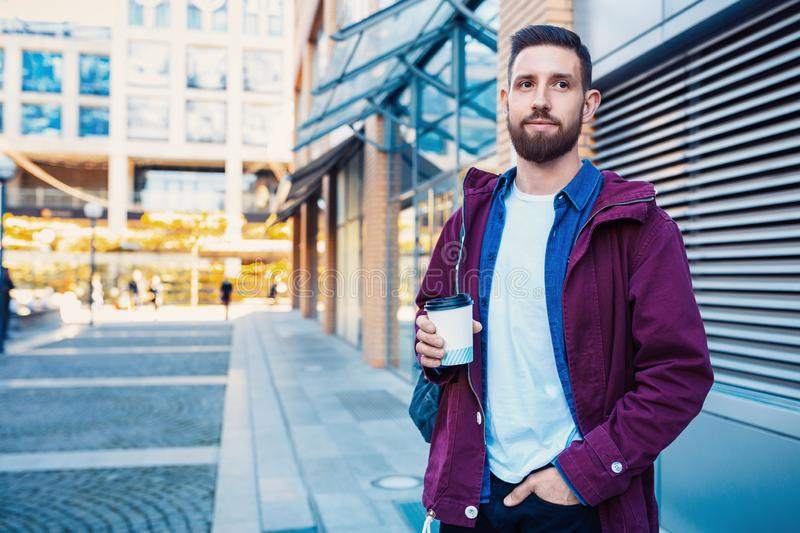 Handsome young man in purple winter jacket drinking coffee. The guy drinking coffee on the street. Man holding paper cup with americano or latte. Street style stock image