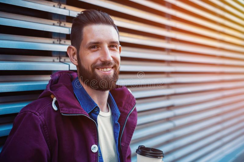 Handsome young man in purple winter jacket drinking coffee. The guy drinking coffee on the street. Sun flare. Handsome young man in purple winter jacket drinking royalty free stock images