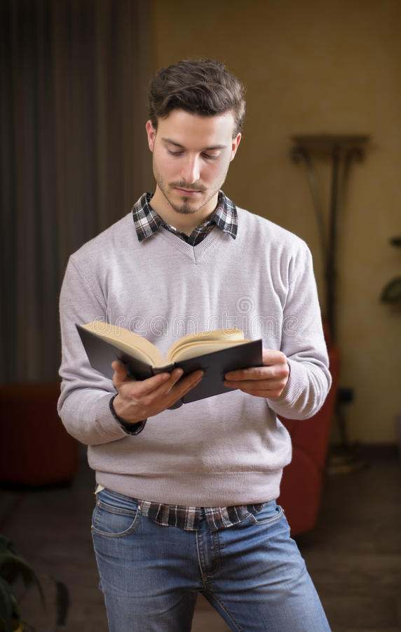 Handsome Young Man Reading Book At Home In His Living-room Royalty Free Stock Photos