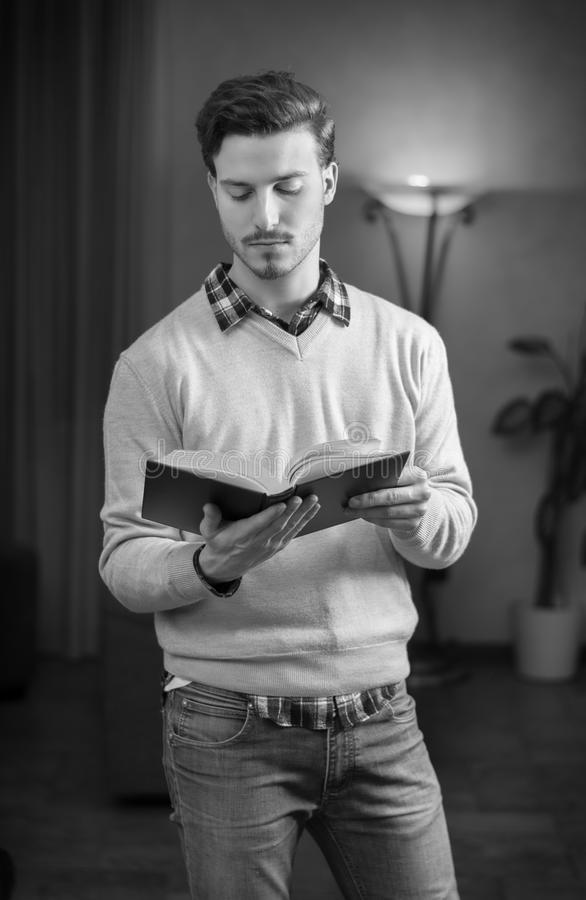 Handsome Young Man Reading Book At Home In His Living-room Royalty Free Stock Photography