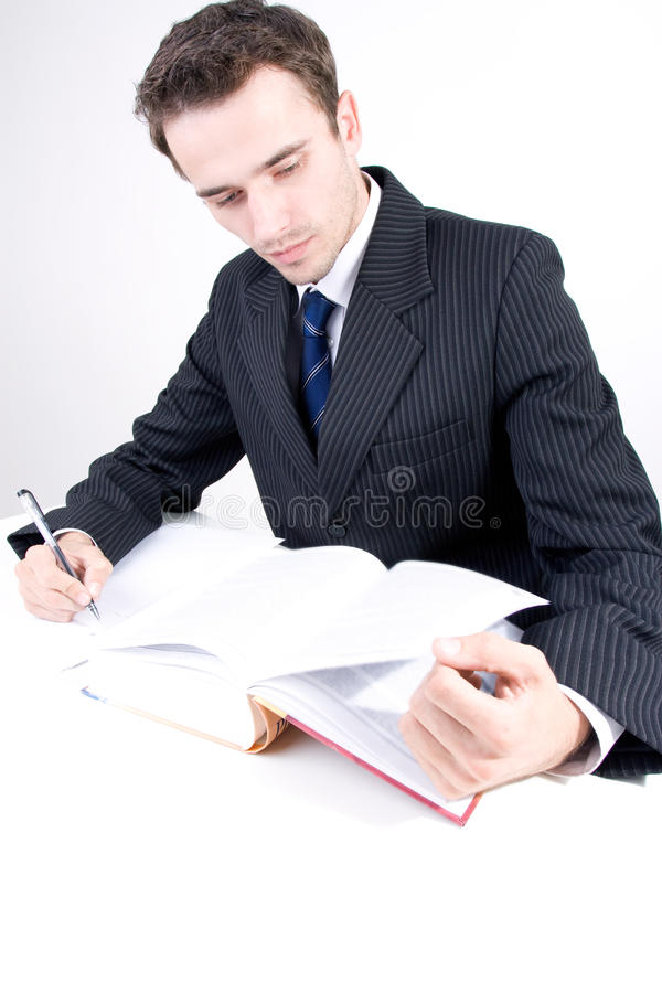Handsome Young Man Reading And Writing In Office Stock