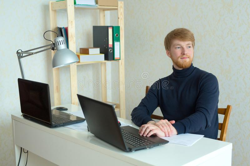 Handsome young man with a red beard working in his office royalty free stock image