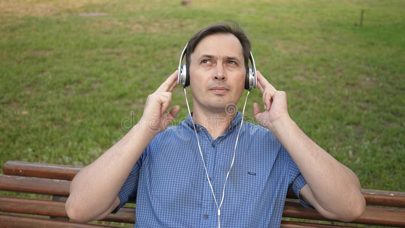 Handsome young man resting in a park listening to music from his smartphone with headphones and dancing outside in a stock image