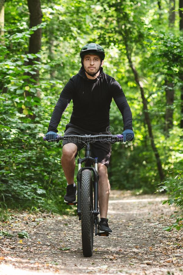 Handsome man riding bike down the forest trail royalty free stock photo