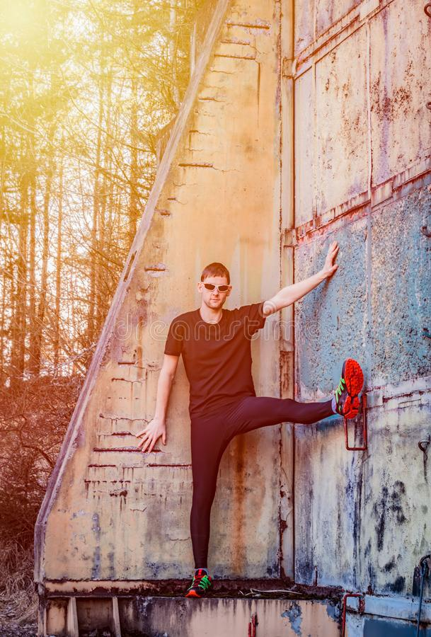 Handsome young man, runner standing on rough wall. Fitness, workout, sport, lifestyle concept royalty free stock images
