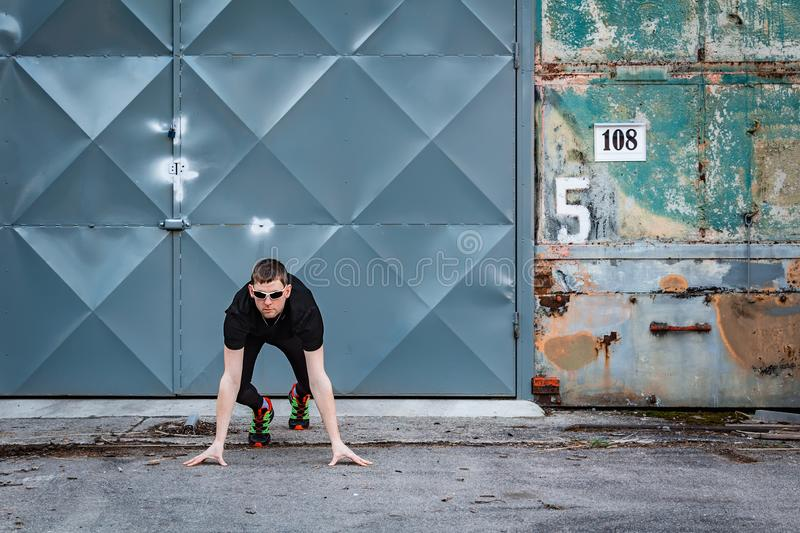Handsome young man, runner in start position from front with door and rough wall. Fitness, workout, sport, lifestyle concept stock image