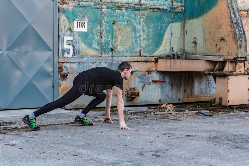 Handsome young man, runner in start position from side with door and rough wall. Fitness, workout, sport, lifestyle concept royalty free stock image