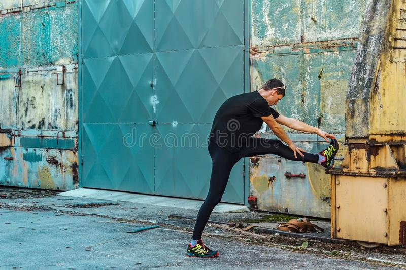 Handsome young man, runner streching on rough wall and door. Fitness, workout, sport, lifestyle concept stock image