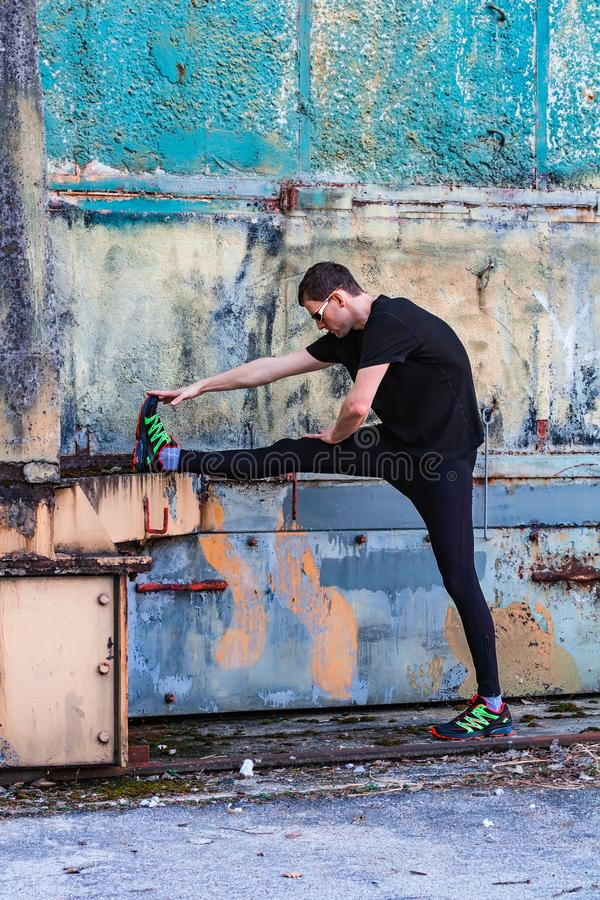 Handsome young man, runner streching on rough wall. Fitness, workout, sport, lifestyle concept stock photos