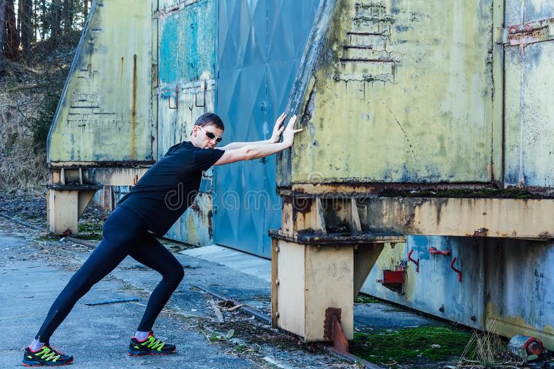 Handsome young man, runner streching on wall and door. Fitness, workout, sport, lifestyle concept royalty free stock photography
