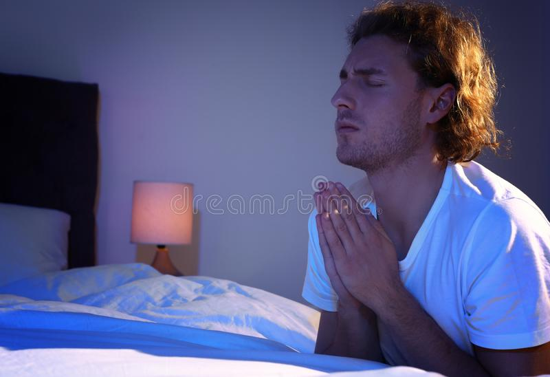 Handsome young man saying bedtime prayer in dark room. At night royalty free stock photography