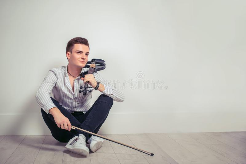 Dreaming young man with violin looking away stock images