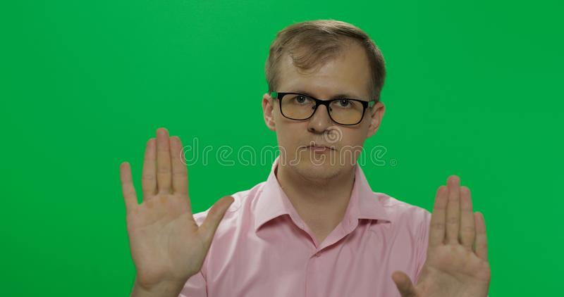 Handsome young man in shirt saying no and doing stop gesture with a hand royalty free stock photography