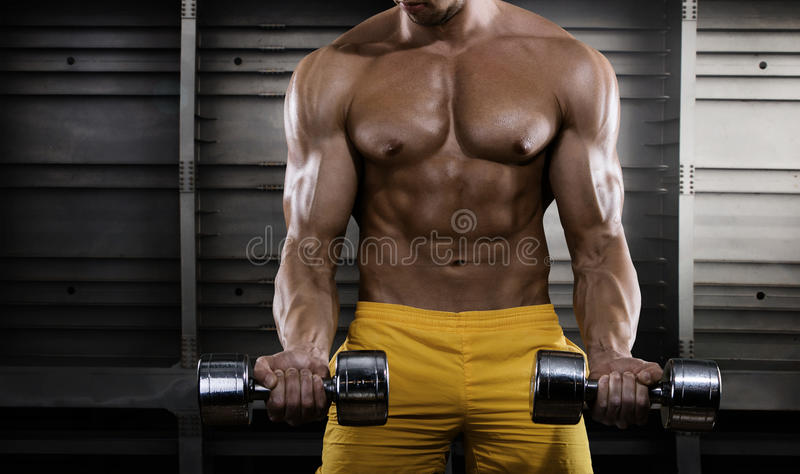 Handsome young man in shorts, doing exercises for biceps stock images