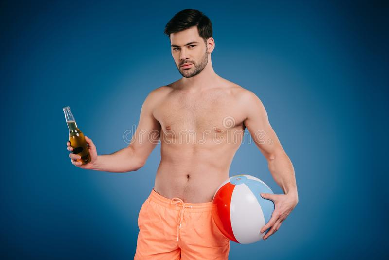 handsome young man in shorts holding bottle of summer drink and inflatable ball and looking at camera stock image