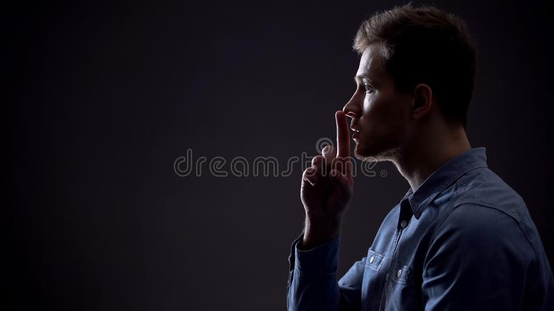 Handsome young man showing silence gesture, mysterious secret, side view stock image