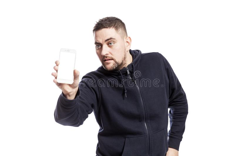 Handsome young man shows a phone with an isolated screen. Isolated over white background royalty free stock image