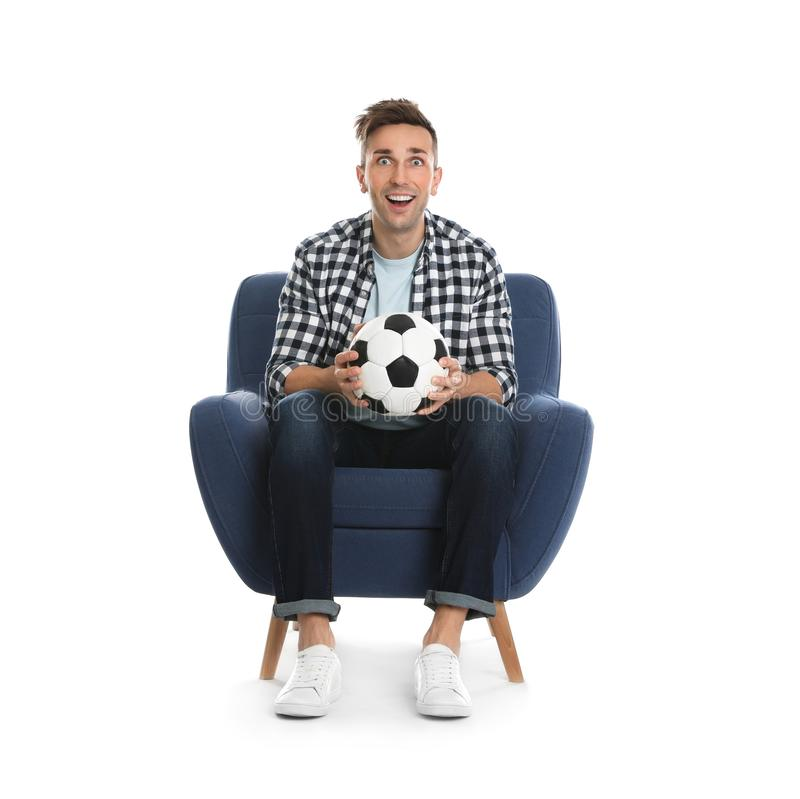 Handsome young man sitting in armchair and watching soccer match on background stock images