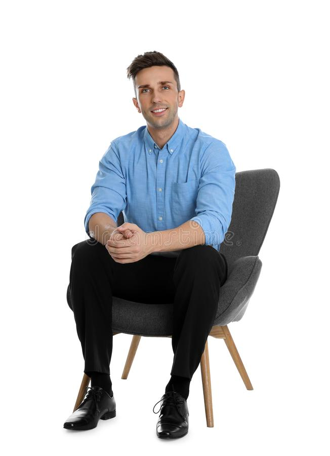 Handsome young man sitting in armchair on background stock photos