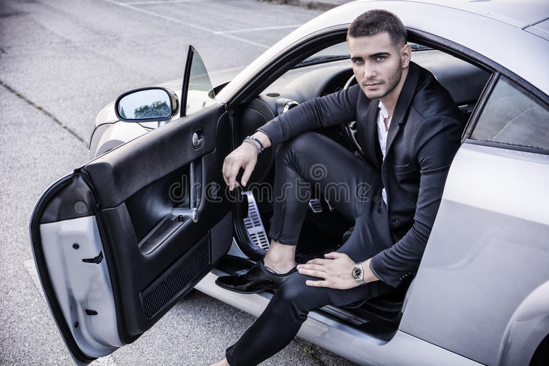Handsome young man sitting in his car stock photography