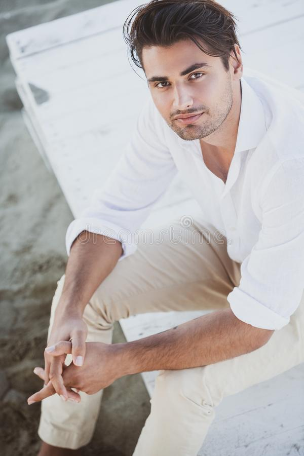 Handsome young man sitting looking up. He wears a white shirt and brown trousers. royalty free stock images