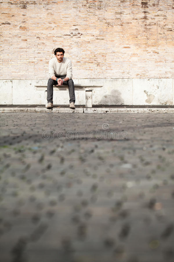 Handsome young man sitting on marble bench with bricks background. A beautiful and young boy sat on a marble bench. Behind him a large, old brick wall. Beside stock photo