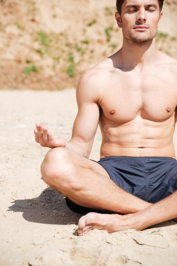 Handsome young man sitting and meditating on the beach royalty free stock photos
