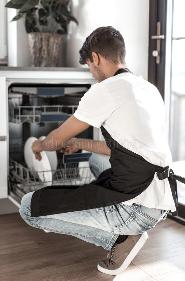 Handsome young man sitting near an open dishwasher stock photography