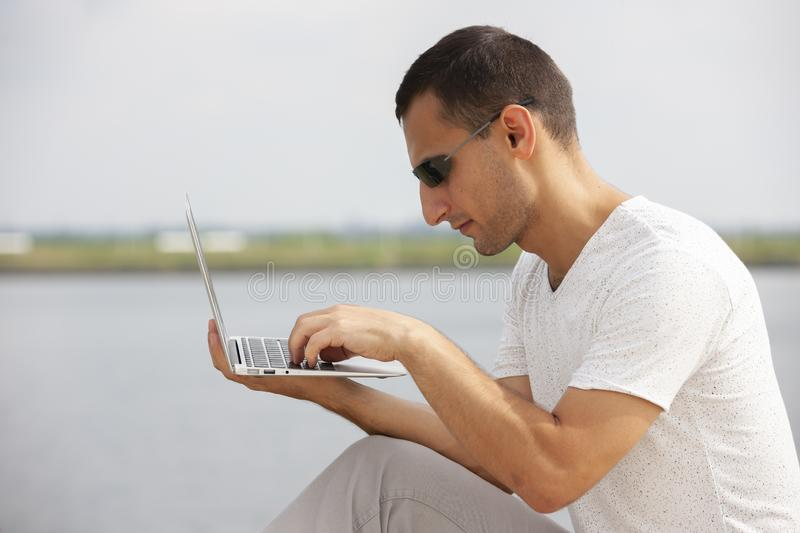 Handsome young man sitting near the sea with a laptop stock images