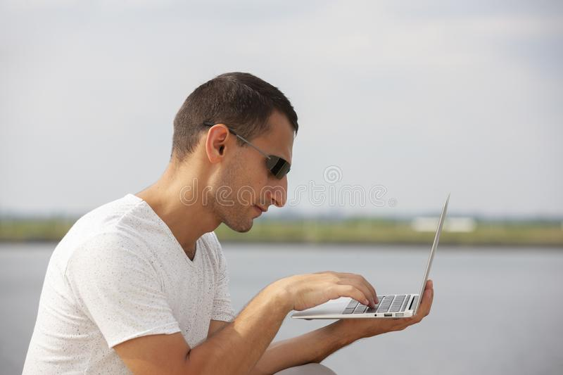 Handsome young man sitting near the sea with a laptop royalty free stock image