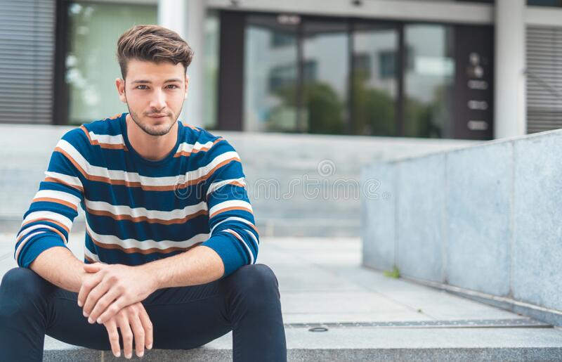 Handsome young man sitting on stairs stock image