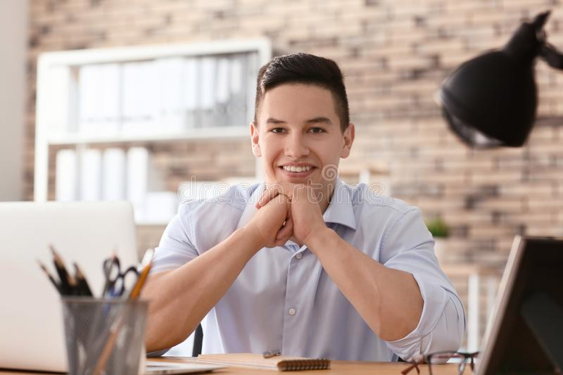 Handsome young man sitting at table in office royalty free stock photography
