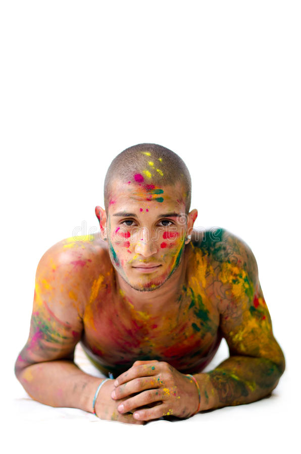 Handsome young man with skin all painted with Honi colors, resting on his elbows. Attractive young man shirtless, skin painted all over with bright Honi colors stock images