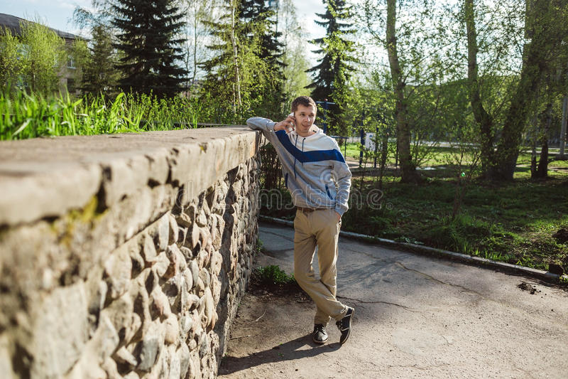 Handsome young man in smart casual wear talking on phone. Shoot outdoors. royalty free stock image