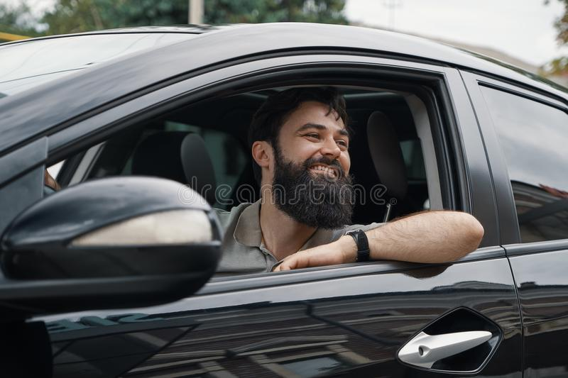 Young man smiling while driving a car. Handsome young man smiling while driving a car. Happy male driver smiling while sitting in a car with open front window royalty free stock photos