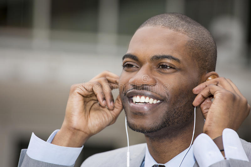 Handsome young man smiling while listening to music royalty free stock photography