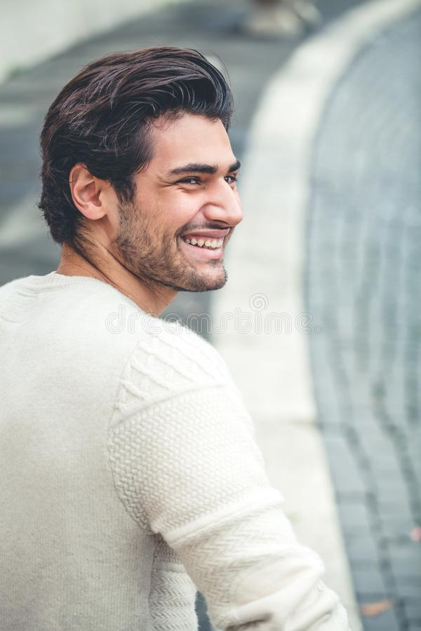 Handsome young man smiling, outdoors. Urban style. Handsome young man smiling. Outdoors, the boy is wearing a white sweater. Trendy hair, and light beard stock photography