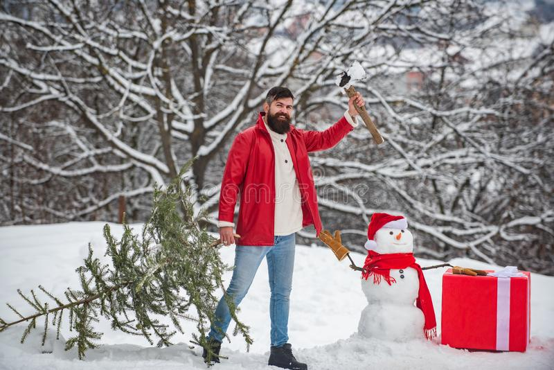A handsome young man with snow man carries a Christmas tree. Merry Christmas and happy new year greeting card. Snowman stock photography