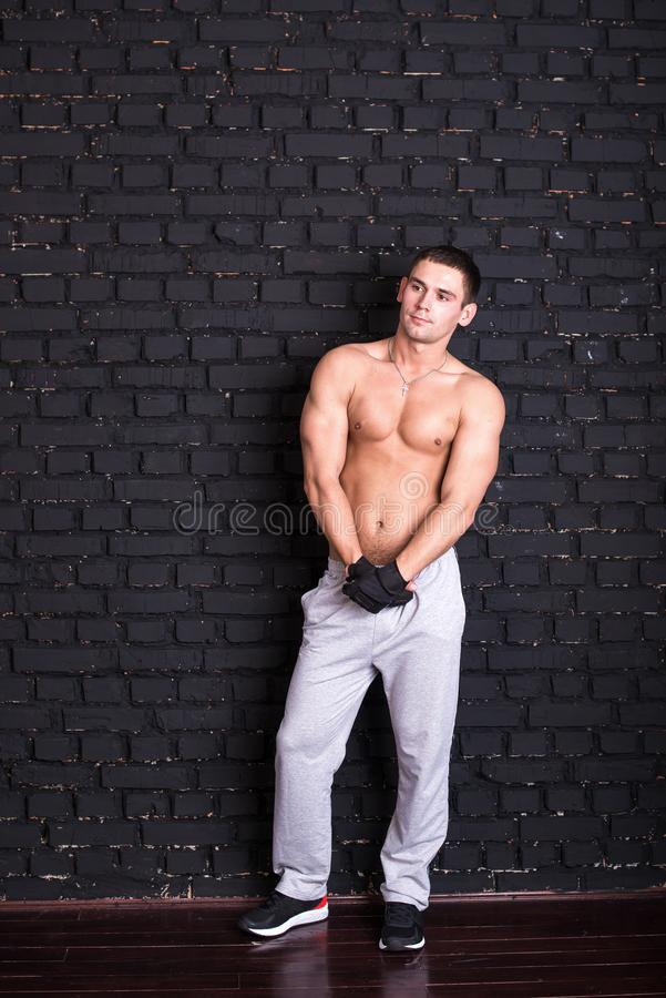 A handsome young man in a sports style with a bare torso, against a black brick wall, a model photo. royalty free stock photos