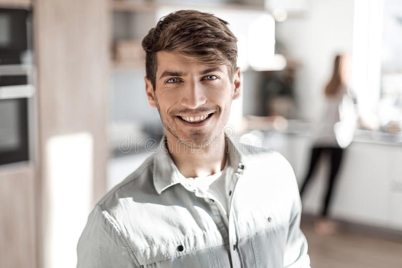 Handsome young man standing in his kitchen. royalty free stock images