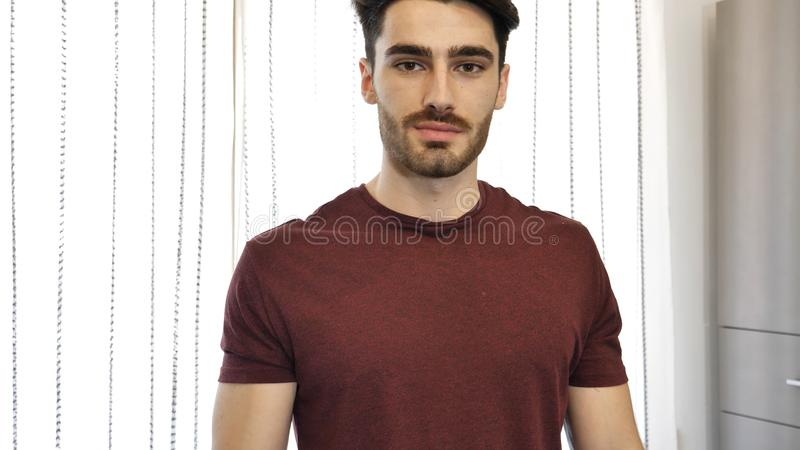 Handsome young man standing at home stock photo