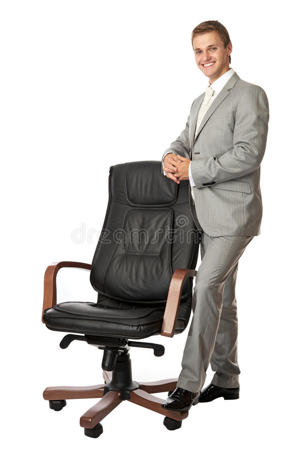 Handsome young man standing next to an armchair stock photo